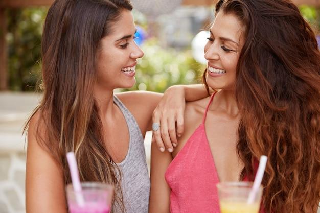 Mulheres morenas lindas e sorridentes olhando felizes nos olhos uma da outra