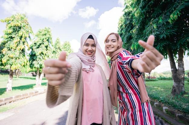 Mulheres muçulmanas asiáticas felizes em hijabs ao ar livre em dia ensolarado com um amigo se abraçando, mostrando um gesto de amor