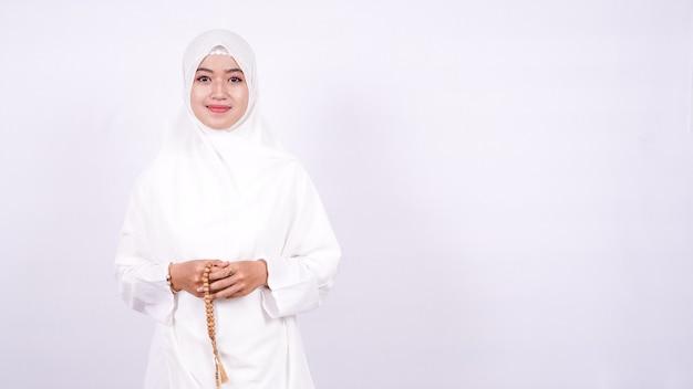 Mulheres muçulmanas asiáticas rezam em uma parede branca