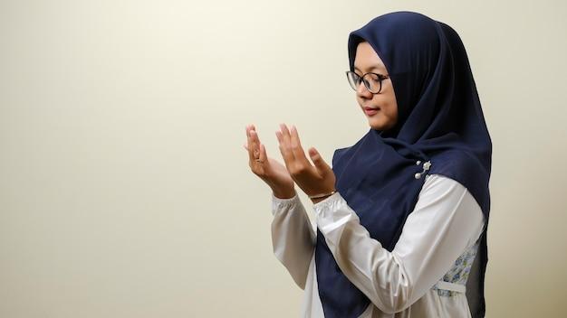 Mulheres muçulmanas asiáticas usando hijab orando com um espaço vazio ao lado dela