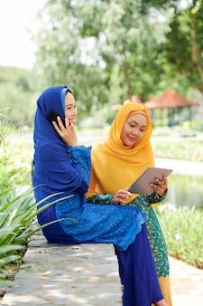Mulheres muçulmanas bonitas com gadgets