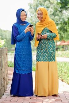 Mulheres muçulmanas bonitas com smartphones