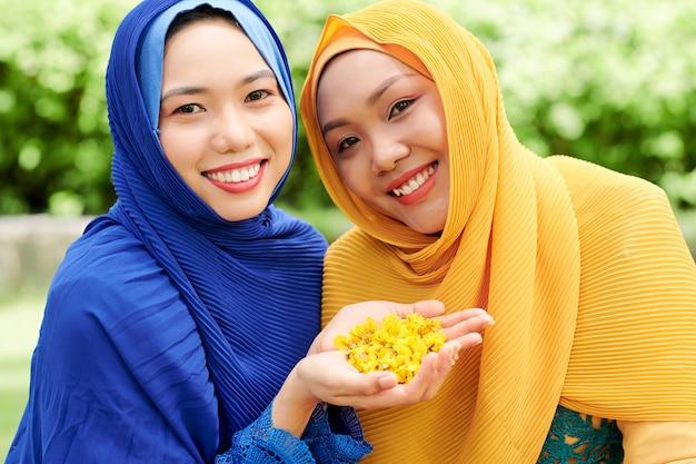 Mulheres muçulmanas com pétalas de flores
