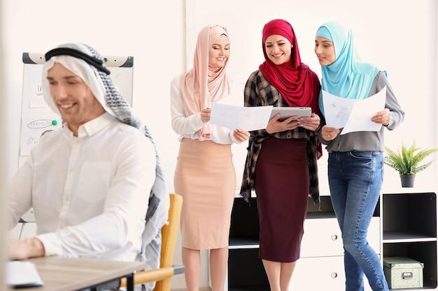 Mulheres muçulmanas com roupas tradicionais no local de trabalho