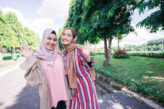 Mulheres muçulmanas em hijabs ao ar livre em dia de sol com um amigo feliz acenando com a mão