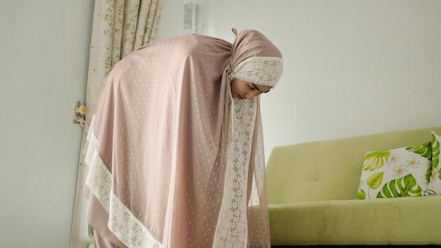 Mulheres muçulmanas oram com um movimento de reverência enquanto usam uma mukenah
