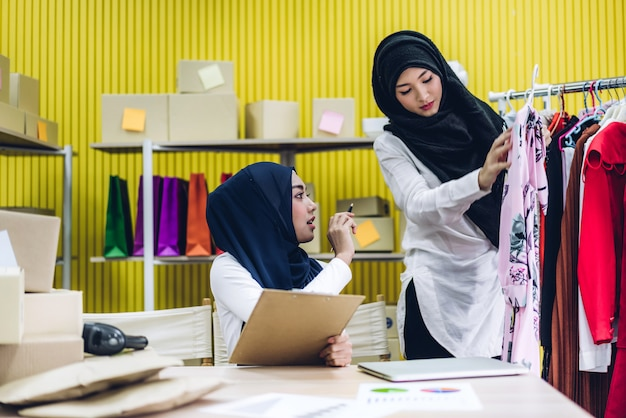 Mulheres muçulmanas que organizam sua loja de roupas on-line