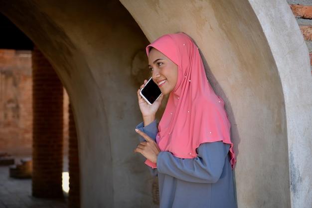 Mulheres muçulmanas usam telefones celulares para entrar em contato com empresas. na velha mesquita em ayutthaya