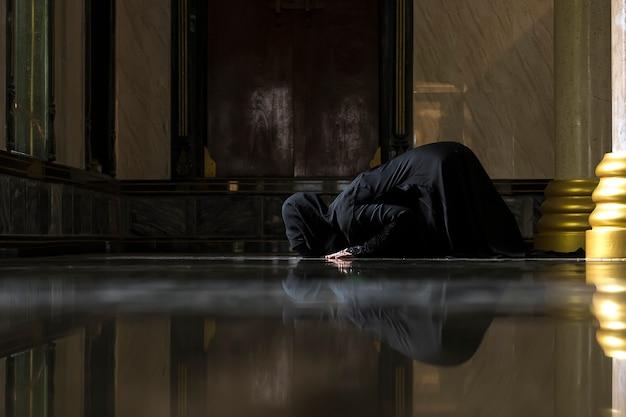 Mulheres muçulmanas vestindo camisas pretas fazendo a oração de acordo com os princípios do islã.