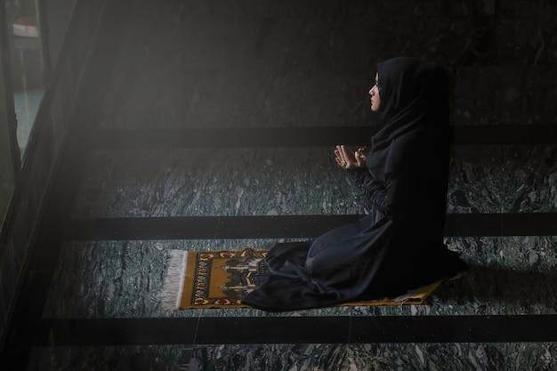 Mulheres muçulmanas vestindo camisas pretas fazendo oração de acordo com os princípios do islã.