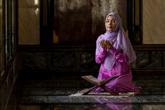 Mulheres muçulmanas vestindo camisas roxas fazendo a oração do islã.