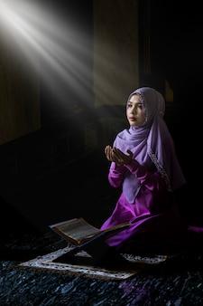 Mulheres muçulmanas vestindo camisas roxas fazendo oração de acordo com os princípios do islã.