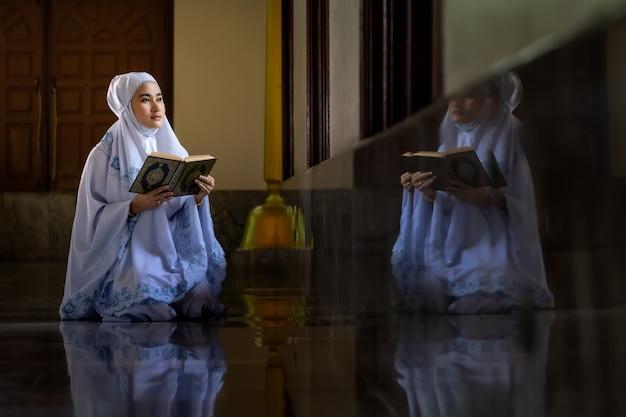 Mulheres muçulmanas vestindo camisetas brancas fazendo orações de acordo com os princípios do islã.