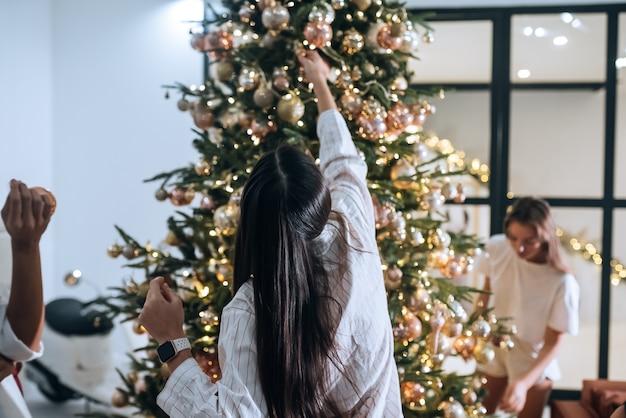 Mulheres muito atraentes decoram a árvore de natal com bolas