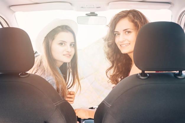 Mulheres muito jovens sentados no carro