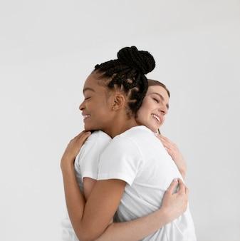 Mulheres multiculturais abraçando um tiro médio