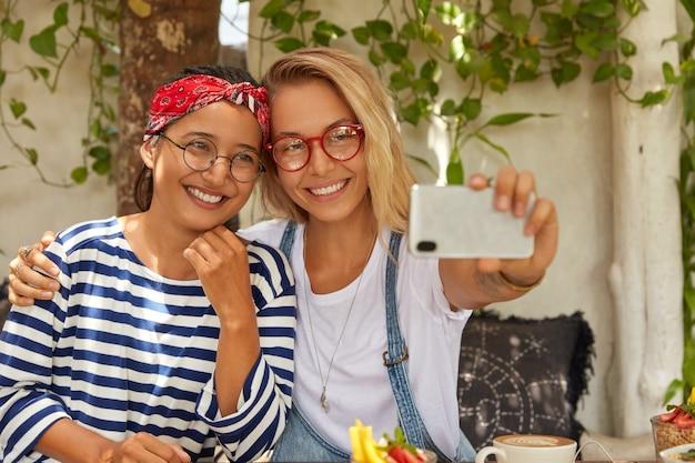 Mulheres multiétnicas amigáveis acariciam e posam no celular, fazem selfie retratos, passam o tempo em um café, comem sobremesa, usam óculos redondos, aproveitam o tempo de recreação, ficam satisfeitas com algo