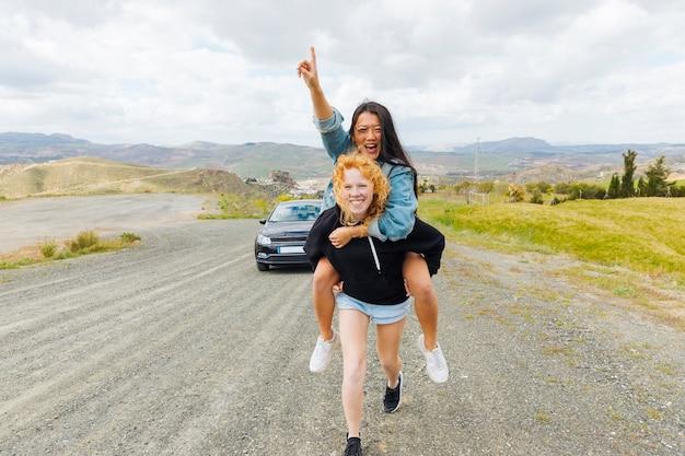 Mulheres multiétnicas, brincando nas costas na beira da estrada