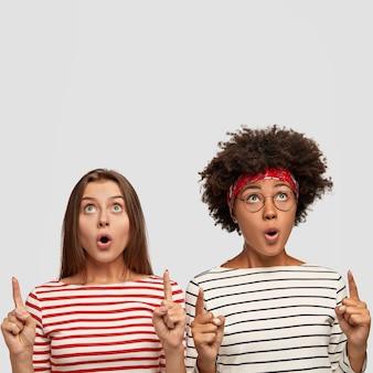 Mulheres multiétnicas chocadas apontam para cima com os dois dedos indicadores