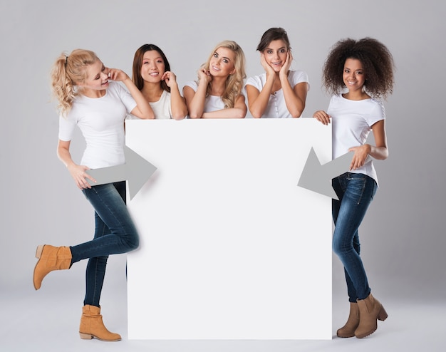 Mulheres multiétnicas com outdoor vazio