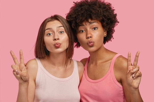 Mulheres multiétnicas fazem beicinho e fazem sinal da paz, ficam próximas umas das outras, posam para fazer uma foto comum, felizes por se conhecerem, vestidas com camiseta casual, isoladas sobre parede rosa
