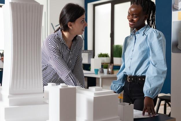 Mulheres multiétnicas trabalhando como arquitetas profissionais parceiras para projetar planos de projeto colega ...