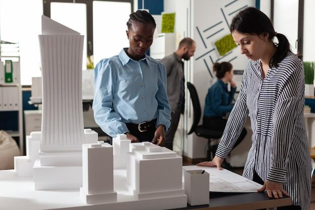 Mulheres multiétnicas trabalhando como arquitetas profissionais parceiras para projetar planos de projeto