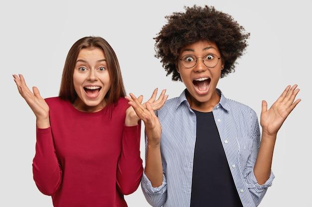 Mulheres multirraciais, com diversidade emocional, apertam as mãos, exclamam em voz alta, vestidas casualmente