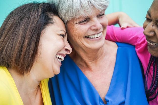 Mulheres multirraciais idosas se divertindo abraçadas ao ar livre - foco no rosto feminino esquerdo