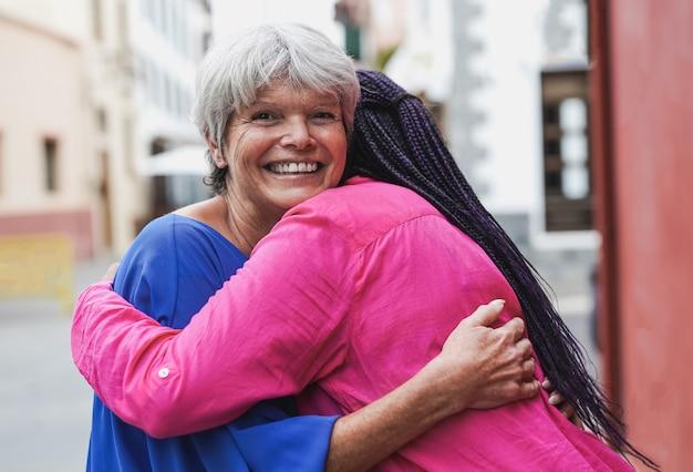 Mulheres multirraciais sênior se abraçando - conceito de amizade, amor e pessoas idosas