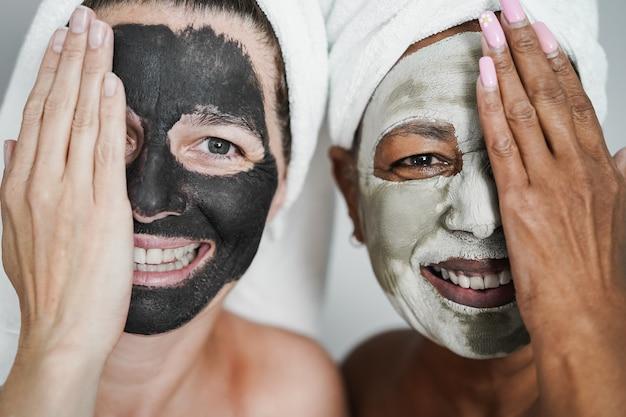 Mulheres multirraciais seniores fazendo tratamento de beleza com máscara de pele - conceito de cuidados com o corpo - foco no rosto feminino direito