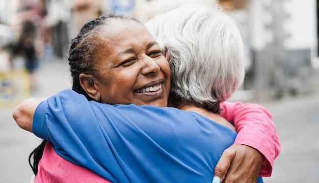 Mulheres multirraciais seniores se encontrando e se abraçando ao ar livre