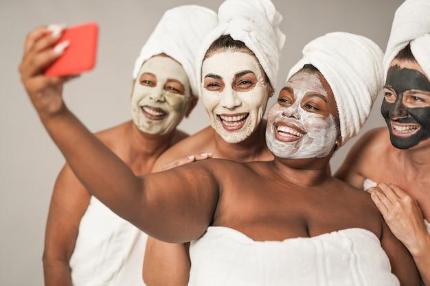 Mulheres multirraciais tirando uma selfie com smartphone - pessoas de várias gerações fazendo tratamentos de beleza juntas