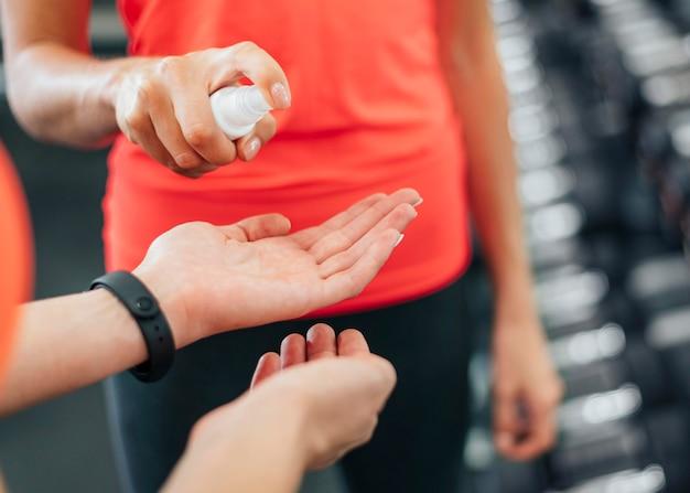 Mulheres na academia desinfetando as mãos