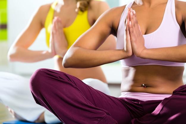 Mulheres na academia fazendo exercícios de ioga para fitness
