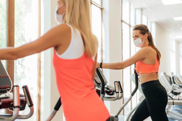 Mulheres na academia se exercitando com máscara facial