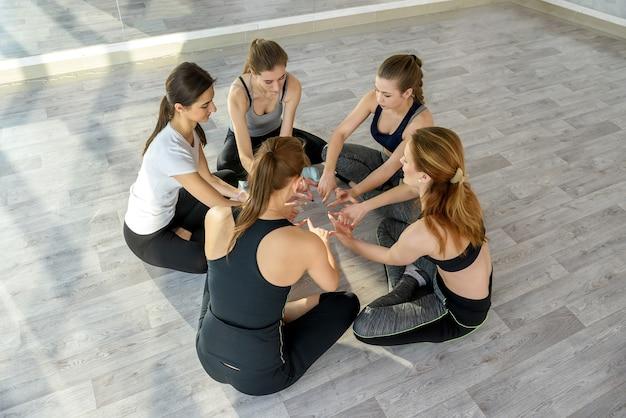 Mulheres na aula de ioga sentadas em círculo no chão