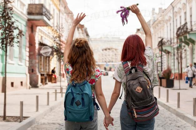 Mulheres na foto do meio caminhando e de mãos dadas
