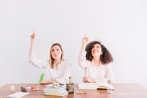 Mulheres na mesa apontando para cima