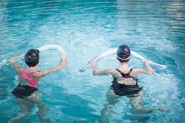 Mulheres na piscina com rolos de espuma no centro de lazer