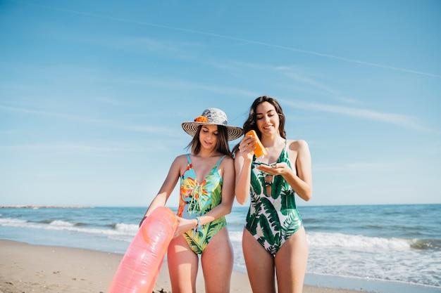 Mulheres na praia com suncream