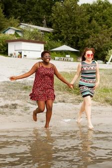 Mulheres na praia de mãos dadas e correndo na água