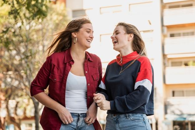 Mulheres na rua rindo um do outro