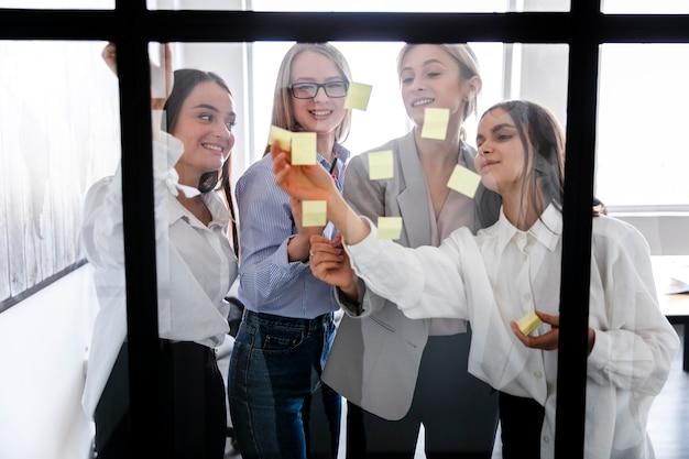 Mulheres no escritório colando notas na janela