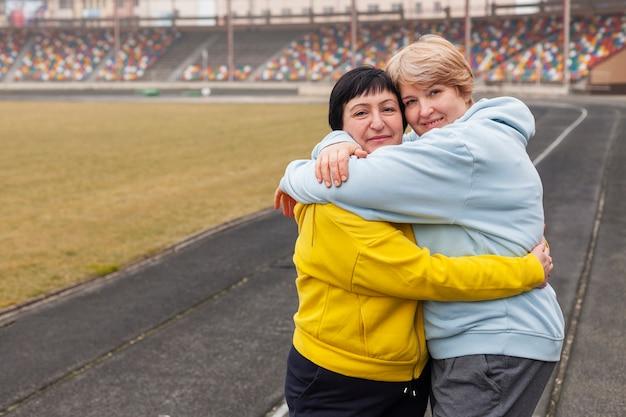 Mulheres no estádio abraçando