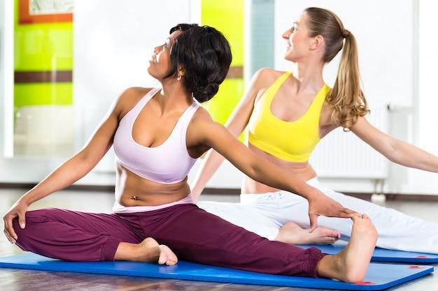 Mulheres no ginásio fazendo exercícios de ioga para fitness