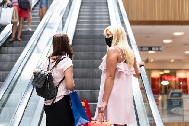 Mulheres no shopping usando máscaras na foto de trás