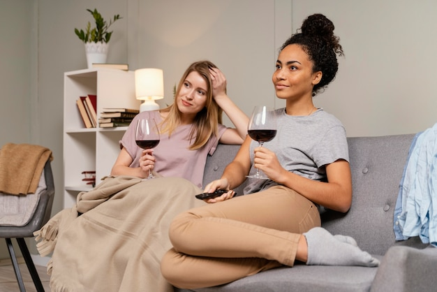 Mulheres no sofá assistindo tv e bebendo vinho