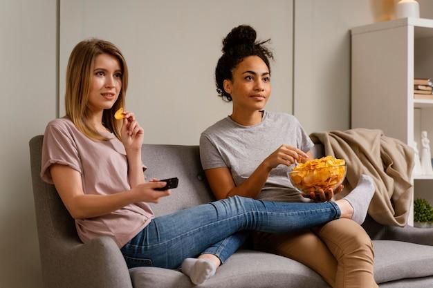 Mulheres no sofá assistindo tv e comendo batatinhas