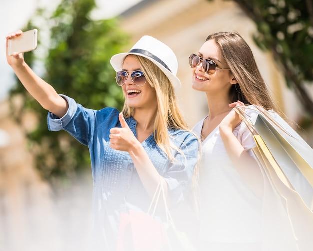 Mulheres nos óculos de sol que tomam um selfie com seu telefone celular.